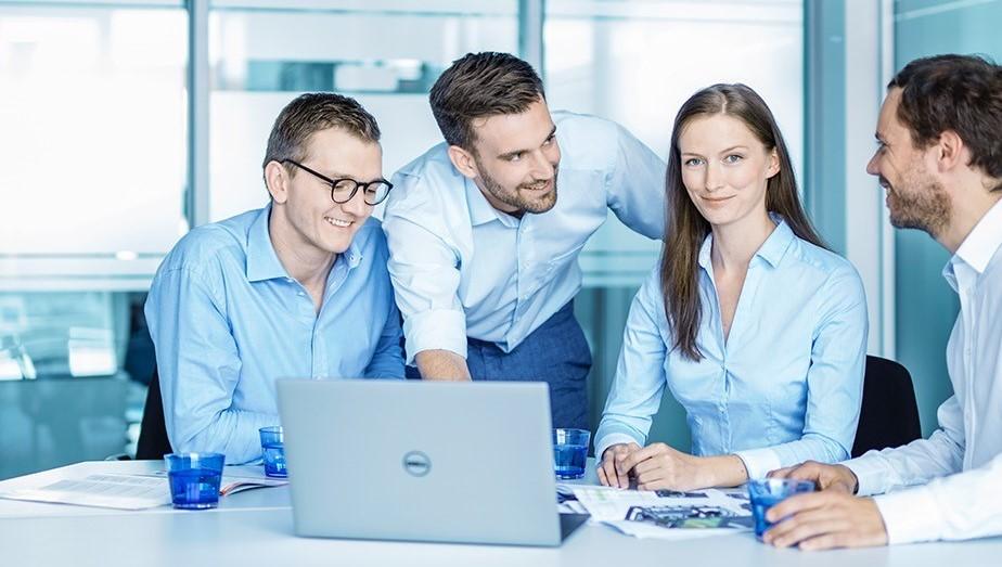 Gruppenbild MELAG Mitarbeiter vor Laptop