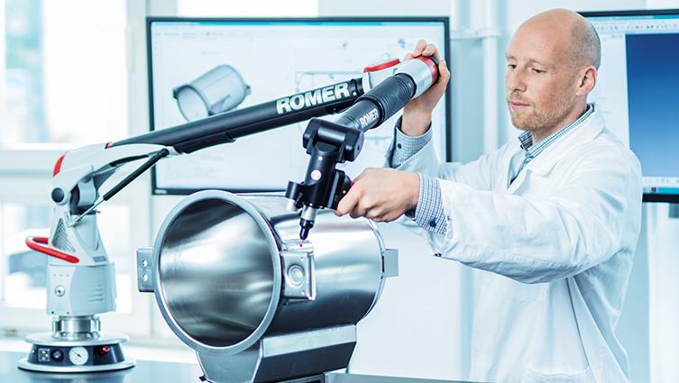 Mann testet mit Präzisionsmaschine Autoklav-Kessel für Qualitätssicherung, hinten 2 Bildschirme