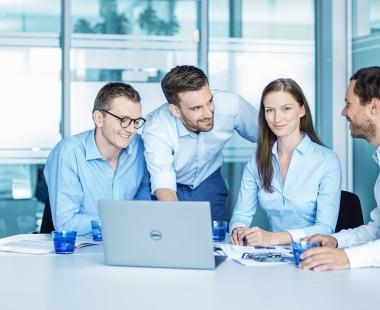 Eine Gruppe glücklicher MELAG Mitarbeiter sitzt zusammen beim Meeting