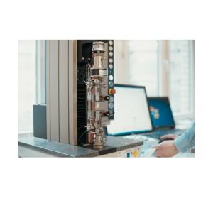 Schrägansicht Zugfestigkeitsprüfmaschine neben Computer Display