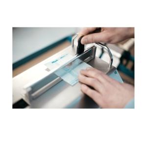 Hand schneidet Sterilgutverpackung MELAfol mit Siegelgerät