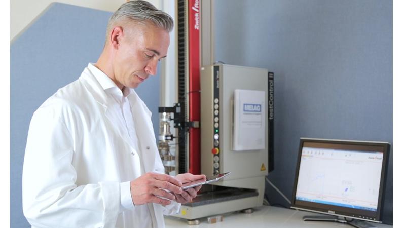 Mann steht vor Zugfestigkeitsprüfmaschine und hält Tablet, daneben steht Computer Display